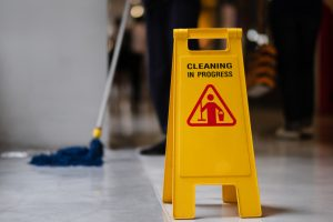 Floor cleaning sign, mop and floor cleaning.