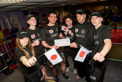Jordon Gill from Marketing & Jordan Wray a Business Development Executive at Datactics presented the Japan team with a cheque for £1000 with ProKick members watching on.