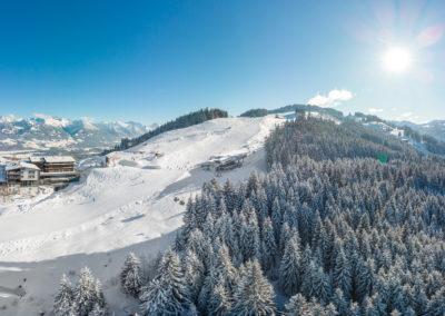 Allgaeuer Berghof Suedseite mit Blick auf die Skipiste- Luftaufnahme im Winter