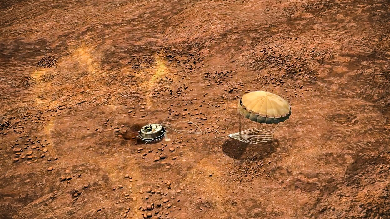 A picture that shows an artist's impression of a probe on the surface of Titan, Saturn's moon. The probe can be seen from above against the orange terrain.