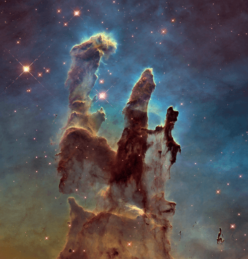 A picture that shows the Pillars of Creation, towers of cosmic dust and gas with a brown color, against a blue background that is full of stars.