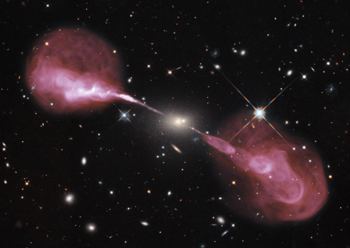 A picture that shows a multitude of stars in space with a supermassive black hole in the middle, which is not visible, with two very massive purple jets of particles.