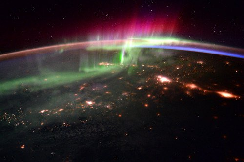 A picture of Earth from low orbit where auroras, or polar lights, are visible.