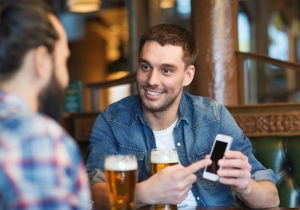 Male Friends With Smartphone Drinking Beer At Bar 54400384