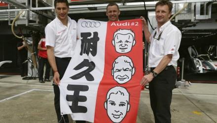 Loïc Duval (F), Tom Kristensen (DK) und Allan McNish (GB) mit einem Banner ihrer japanischen Fans