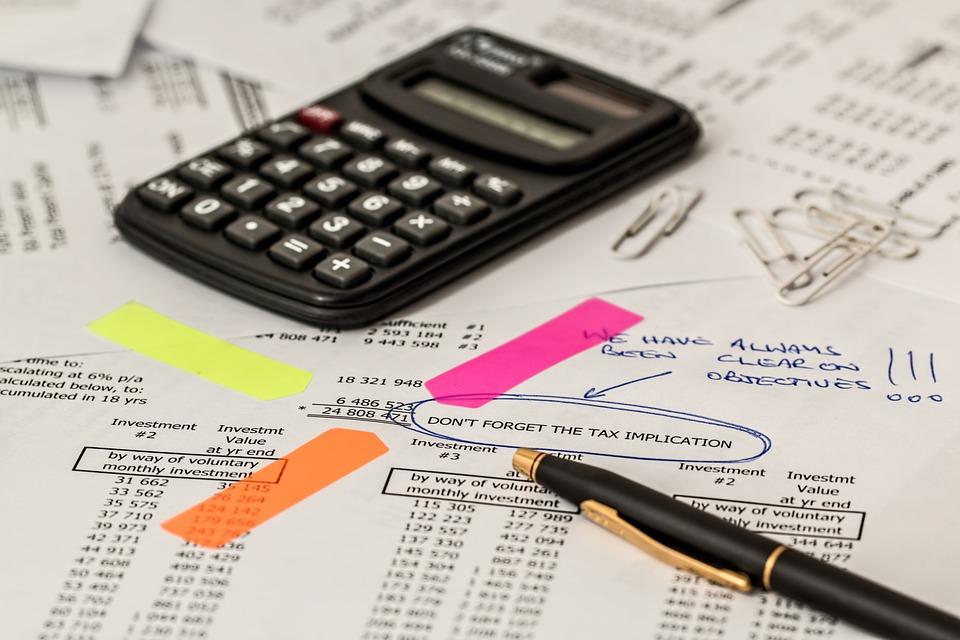 Calculadora con hojas con cálculos debajo