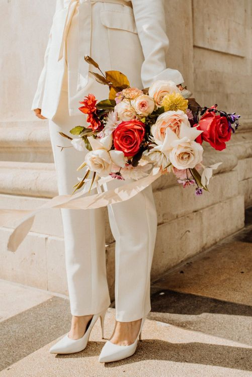 Bright wedding bouquet with bride in white suit