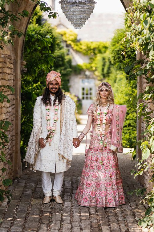 Bride and groom in Indian wedding outfits at The Lost Orangery