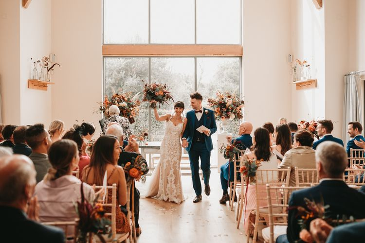 Bride and groom just married at Millbridge Court wedding with Autumn wedding flowers
