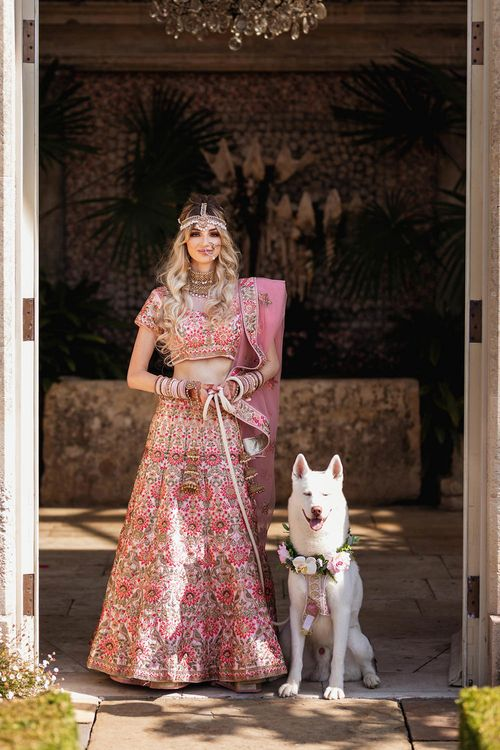 Bride in pink Indian wedding dress with her pet dog