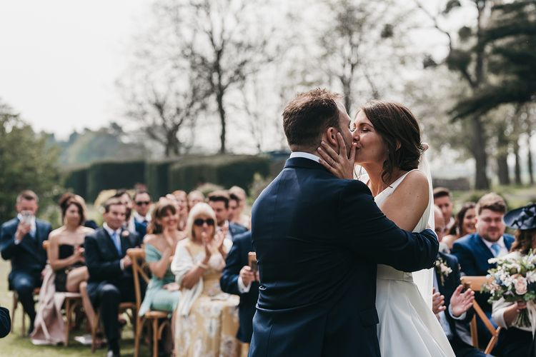Bride and groom kiss at outdoor wedding ceremony at Brinsop Court