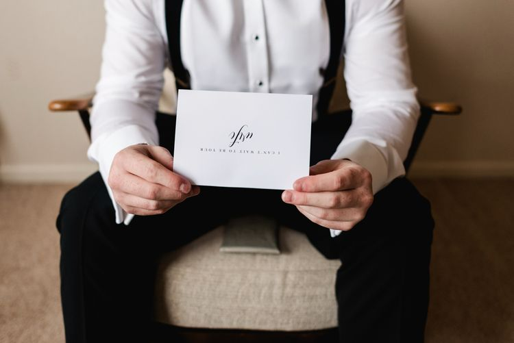 Groom reading a card from his fiance on the morning of the wedding