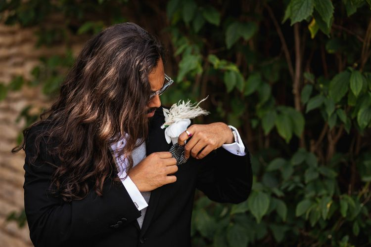 Groom in black suit putting on his white rose buttonhole