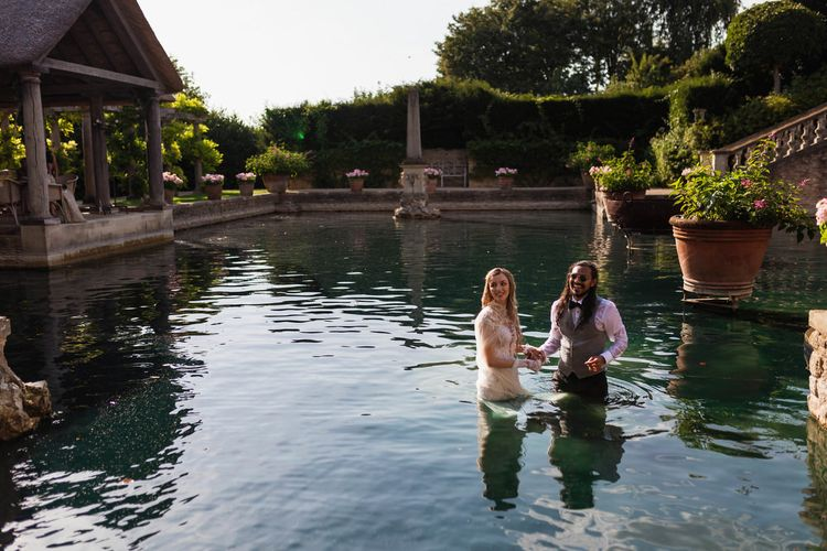Bride and groom in the water at The Lost Orangery