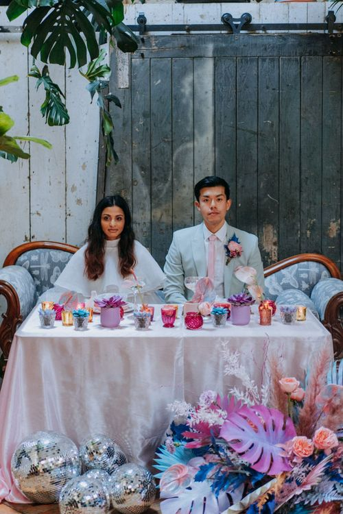 Bride and groom dining at their holographic pastel sweetheart table