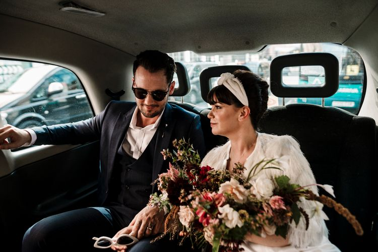 Bride and groom riding in a taxi at Liverpool wedding