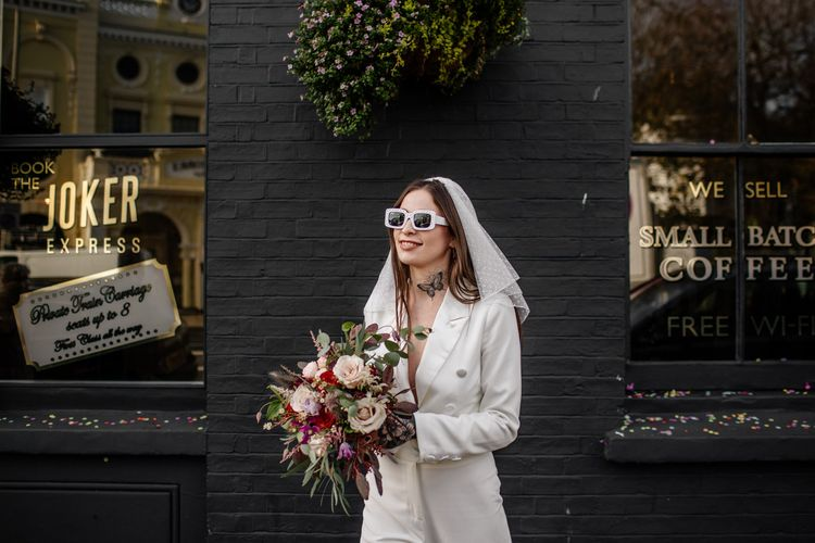 Alternative bride in jumpsuit and sunglasses at Brighton micro wedding