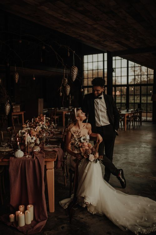 Bride and groom sitting at a winter tablescape with cost candlelight