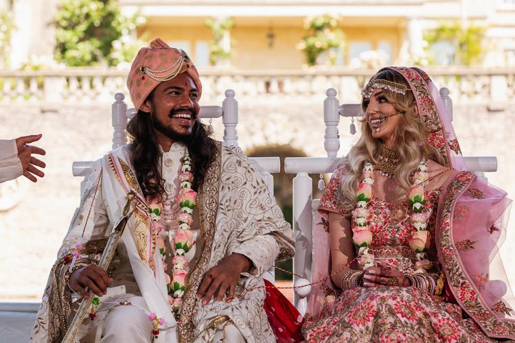 Bride and groom laughing at Hindu wedding ceremony
