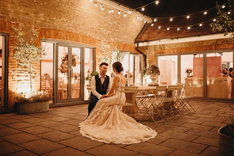 Bride and groom sitting outside Millbridge Court at evening reception with fairy lights