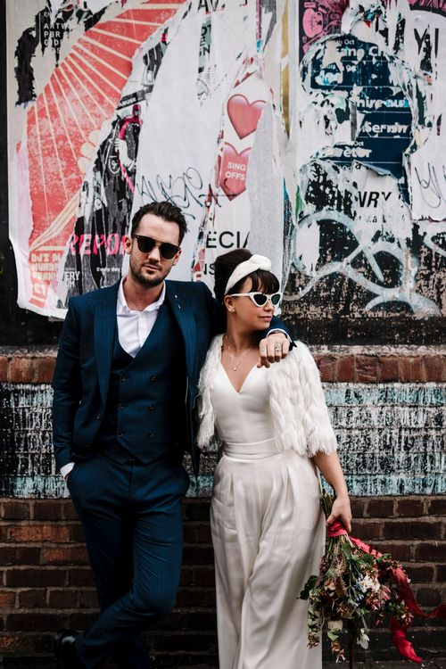 Bride in trouser suit and sunglasses and groom in navy suit and Ray Bans