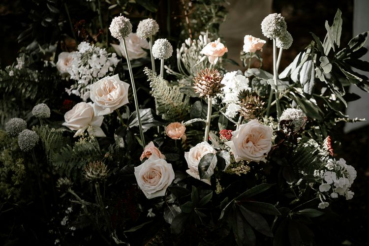 blush pink and foliage wedding flower arrangements in the woods