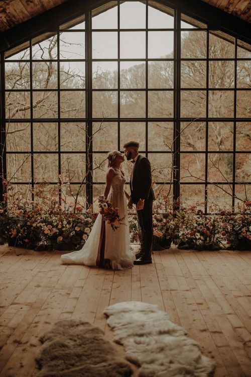 Bride and groom standing in front of the Crittal windows at Hidden River Cabins
