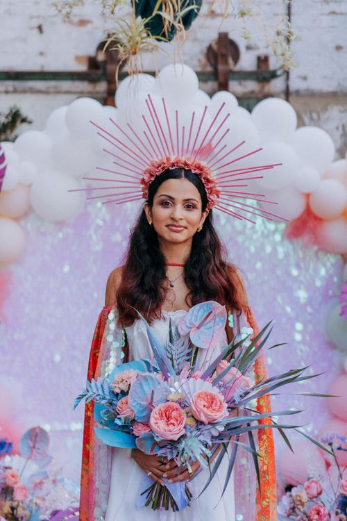 Stylish bride at festival inspired wedding with crown, cape and boots