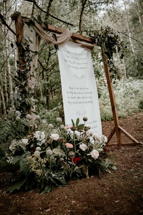 Wooden frame in the woods with fabric sign and locally sourced flowers