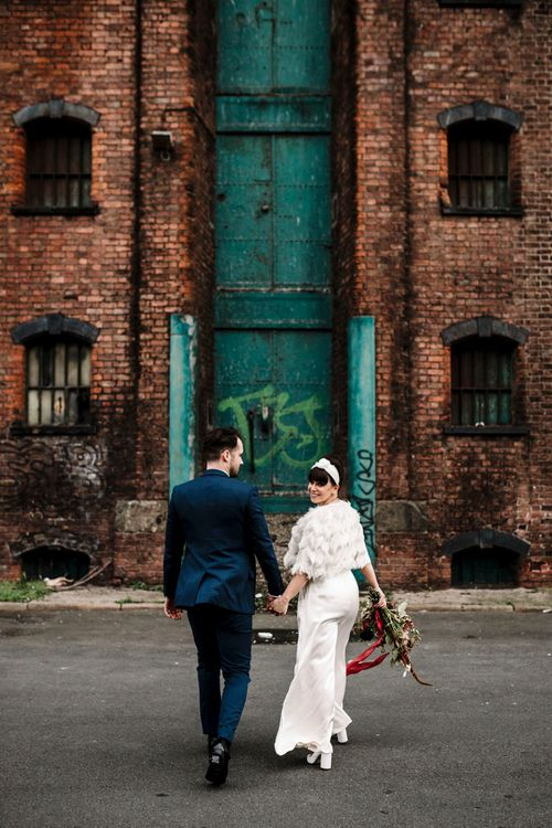 Groom in trouser suit and turban headband walking through the streets at Liverpool wedding