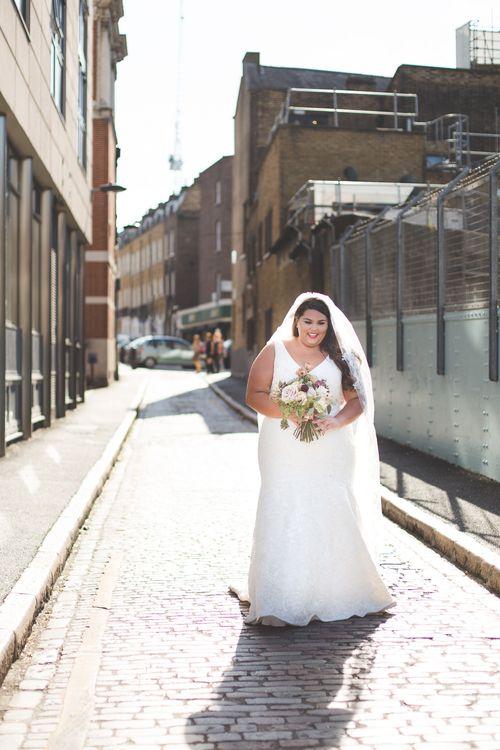 Bride is wedding dress walking down a street