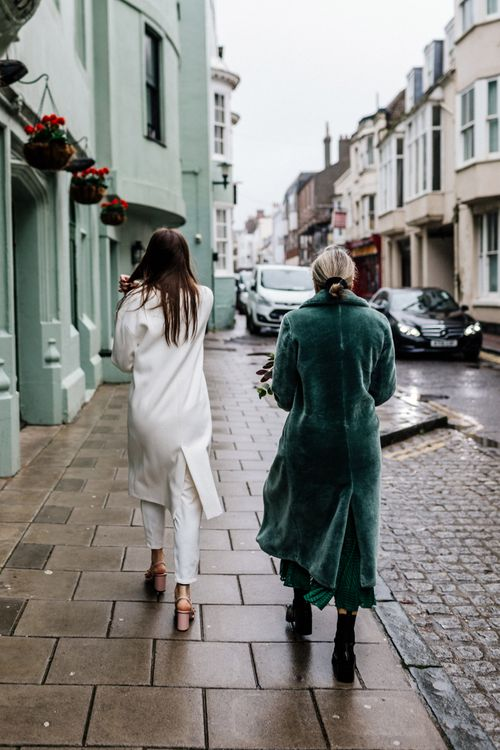 Bride in ivory coat and mother o the bride in green faux fur coat