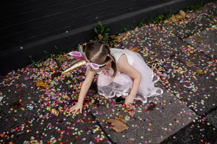 Flower girl with unicorn headband playing with the confetti
