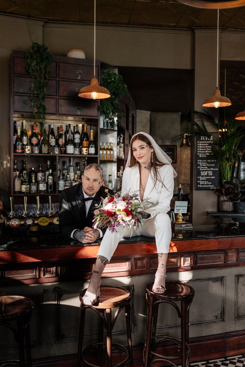 Bride and groom sitting on the bar at Brighton pub reception