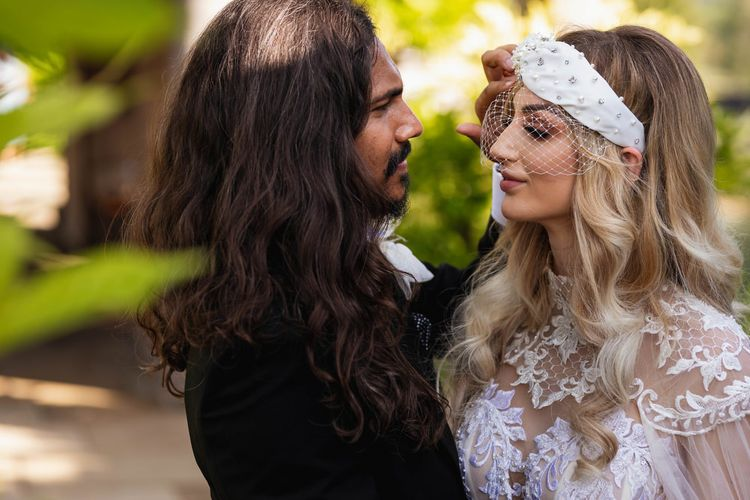 Wedding portrait of groom with long hair and bride in wedding headband