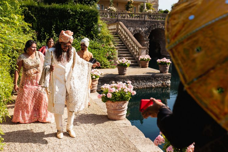 Groom in white and gold Indian outfit arriving for the intimate ceremony