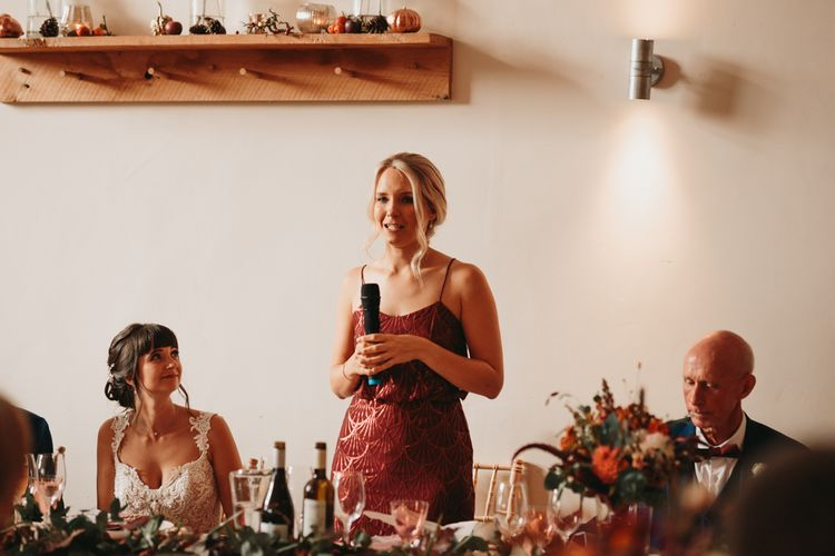 Bridesmaid in rust coloured dress delivering a speech