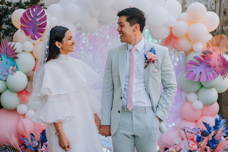 Bride in short wedding dress and boots and groom in pale green suit holding hands