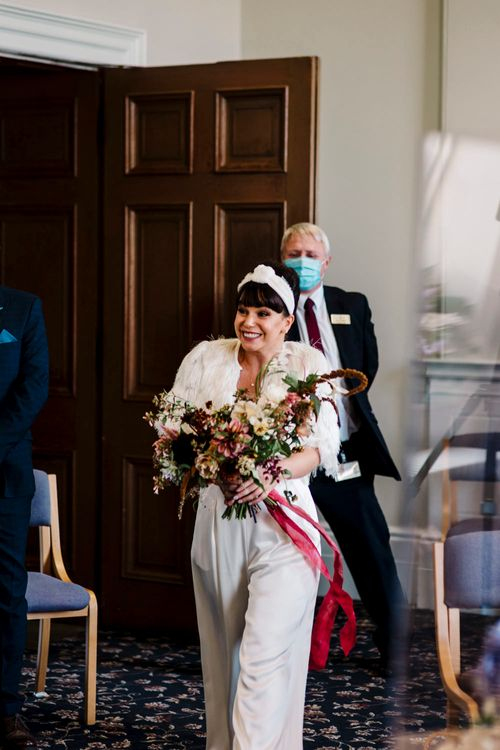 Wedding ceremony bridal entrance in trouser suit and headband