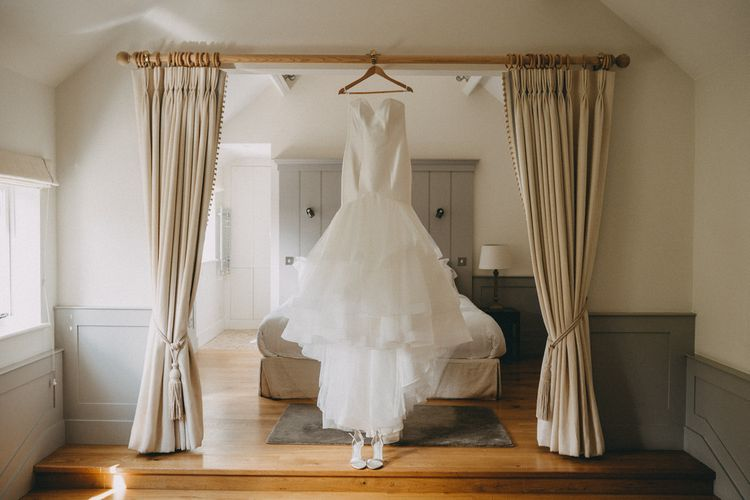 Wedding dress hanging from 4 poster bed