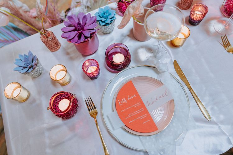 Place setting with colourful stationery and votives