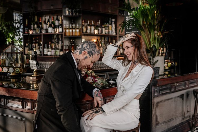 Tattooed bride and groom sitting at the bar of their pub wedding