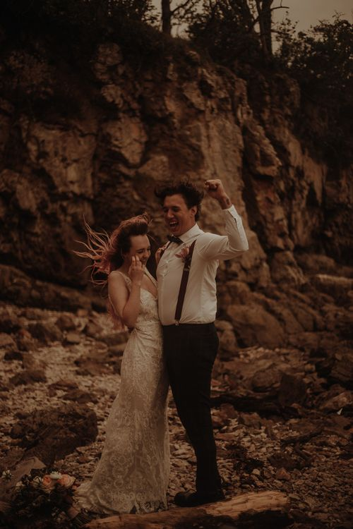Bride in lace wedding dress and groom in braces at elopement wedding