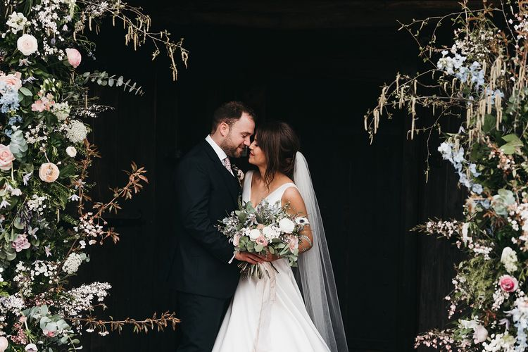 Bride and groom with wedding flowers at Brinsop Court