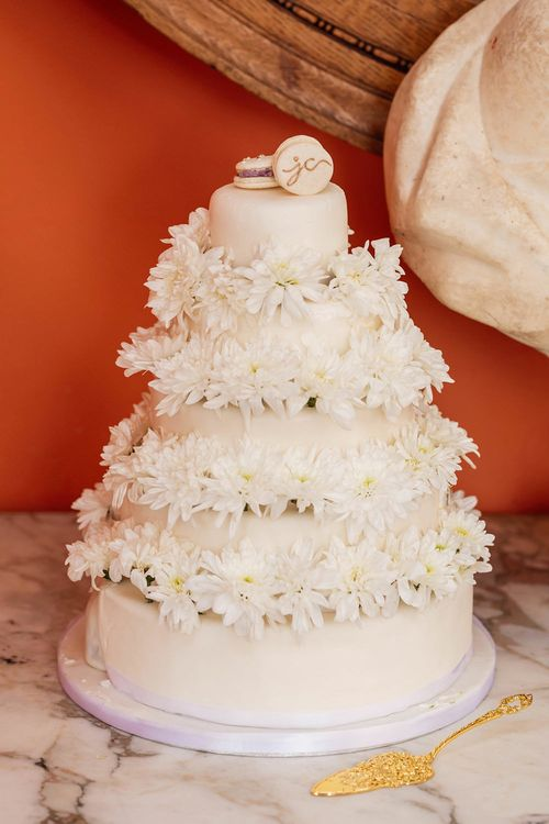 White iced wedding cake with flower decor and macaroon cake toppers
