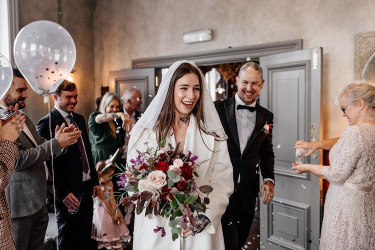 Bride in jumpsuit and polka dot veil entering the pub wedding reception