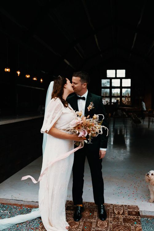 Bride and groom kissing in wedding portrait