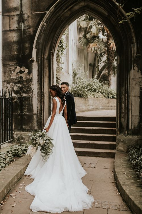 Bride in stunning wedding dress with long train at Devonshire Terrace wedding