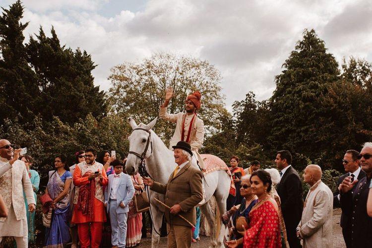 Groom arriving by horse to Hindu wedding
