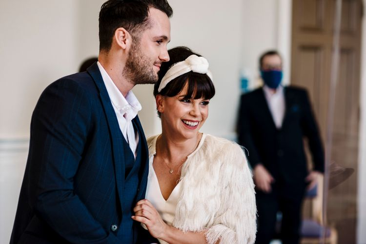 Bride and groom smiling during intimate registry office wedding ceremony